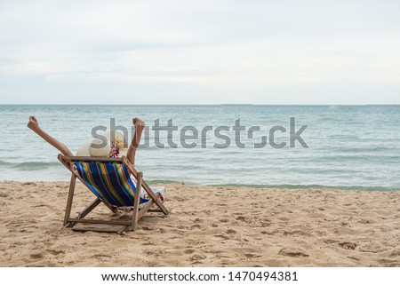 Summer beach vacation concept, Happy young Asian woman with hat relaxing on beach chair and raised hands up. #1470494381
