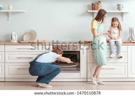 Housewife with daughter and worker repairing oven in kitchen #1470510878