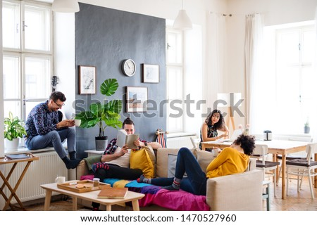 A group of young friends relaxing indoors, house sharing concept. #1470527960