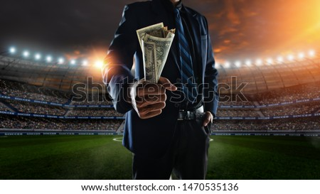 businessman holding large amount of bills at Soccer stadium in background #1470535136