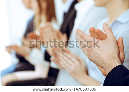 Business people clapping and applause at meeting or conference, close-up of hands. Group of unknown businessmen and women in modern white office. Success teamwork or corporate coaching concept #1470537335