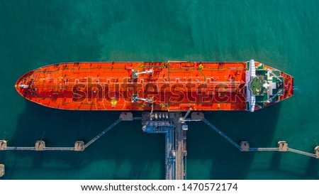 Aerial view tanker ship vessel unloading at port, Business import export oil and gas petrochemical with tanker ship transportation oil from dock refinery, Loading arm oil and gas offshore platforms. Royalty-Free Stock Photo #1470572174