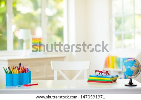 Back to school. Kids bedroom with wooden desk, books, globe, backpack, glasses and pencils. White room with big window for young child. Home interior for girl or boy. Table for homework and study. #1470591971
