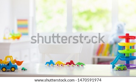 Little boy room. Desk with colorful toy cars. Nursery for young kid with educational vehicle and transport toys. Plastic car at rainbow parking garage. Home or kindergarten interior.  #1470591974