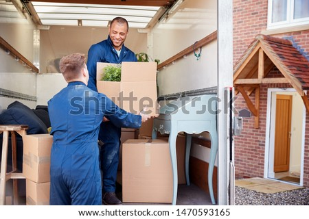 Removal Company Workers Unloading Furniture And Boxes From Truck Into New Home On Moving Day #1470593165