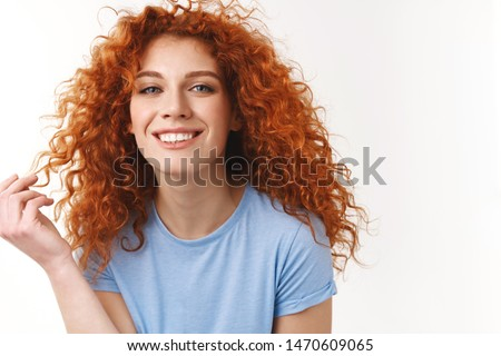 Tenderness, beauty, haircare concept. Alluring sensual young woman with natural curly red hair, rolling strand on finger silly, smiling toothy looking happy and coquettish, standing white background #1470609065