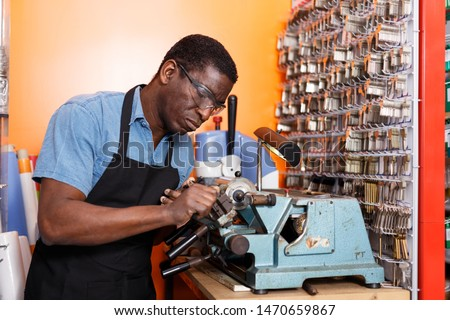 Focused locksmith working on key duplicating machine in workshop #1470659867