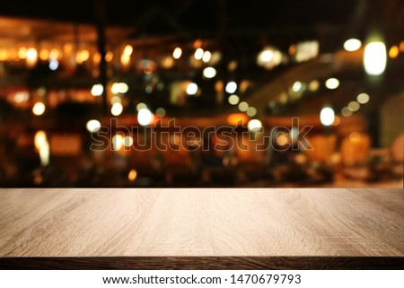 background Image of wooden table in front of abstract blurred restaurant lights #1470679793