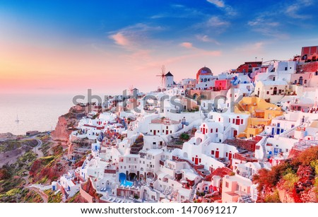 Greece, Santorini island. Charming view of Oia village, traditional Greek white houses and mill at amazing dramatic sunset sky. Oia (Ia) on Santorini is famous and popular travel destination in Europe #1470691217