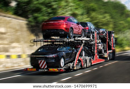 Hauling cars. A car carrier trailer, known variously as a car-carrying trailer, car hauler, auto transport trailer. Photo in motion. Panning. New and very expensive cars transportation.  #1470699971