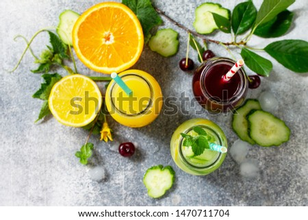 Various refreshments drinks - detox cucumber water, cherry juice and orange juice on stone table. Top view flat lay. #1470711704