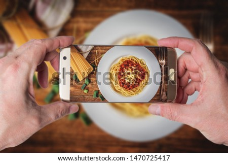 Man taking photo of Italian spaghetti bolognese with tomato sauce and meat