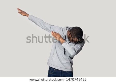 Happy young african american guy in sportswear performing show dance, making dab move gesture. Cheerful black millennial man presenting popular internet meme pose, isolated on grey studio background.