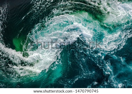 Waves of water of the river and the sea meet each other during high tide and low tide. Whirlpools of the maelstrom of Saltstraumen, Nordland, Norway Royalty-Free Stock Photo #1470790745