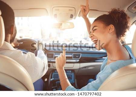 Happy afro couple driving in car and girl singing song, enjoy tavel by auto #1470797402
