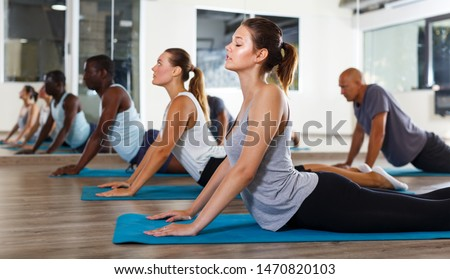 Young people doing stretching exercises before dance training in modern studio #1470820103