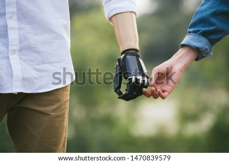 CloseUp Shot Of Man With a prosthetic limb Holding Hands With Female Partner, gentle touch, outdoor image #1470839579