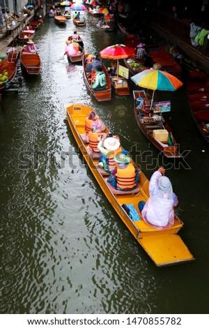 Ratchaburi - Thailand July 5, 2019, Damnoen Saduak floating market on rainy days, tourists wear rainwear #1470855782