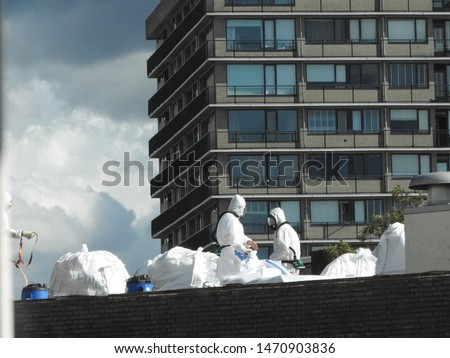 Removal asbestos. Workers with vacuum cleaner, special suit and mask on construction site. Protection against fibers and dust.White bags on roof with asbestos. Threatening background. Part of a serie. #1470903836