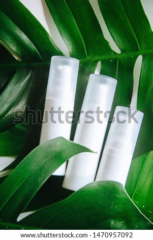 three white plain products lay on green leaves #1470957092