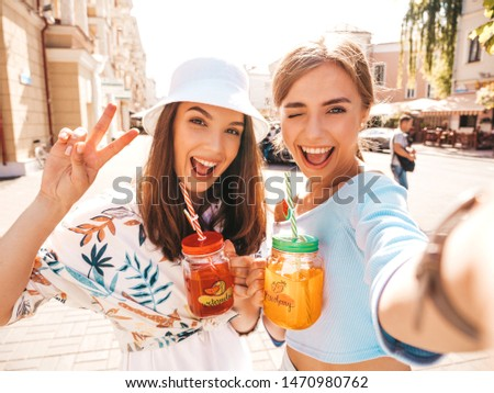 Two young beautiful smiling hipster girls in trendy summer clothes.Panama hat.Sexy carefree women taking selfie portrait photos on smartphone in the street.Drinking fresh cocktail smoozy drink