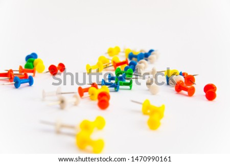 Multi-colored pushpins scattered over a white-grey background. Isolated. Sideview. Selective focus #1470990161