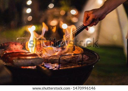 Family making barbecue in dinner party camping at night #1470996146