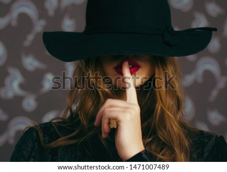 a young girl, long wavy hair, big red lips. Shooting in the room closeup . In the hat, asking for silence #1471007489