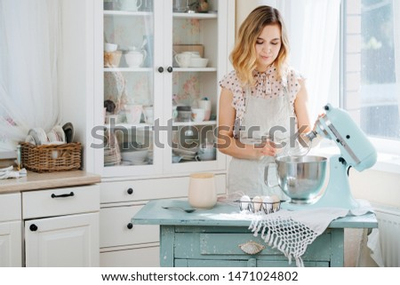 beautiful girl preparing dough in a food processor while standing in a bright kitchen #1471024802