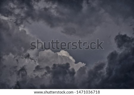 Dark gray and black gloomy rain clouds in the sky, storm, hurricane. Spectacular picture