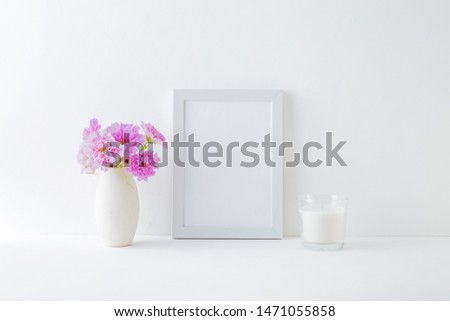 Mockup with a white frame and pink flowers in a vase on a white table #1471055858
