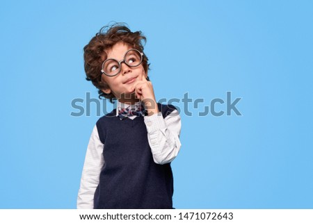Smart wunderkind in nerdy glasses and school uniform touching cheek and looking up while thinking against blue background