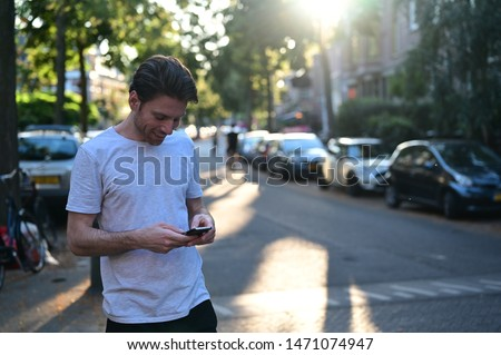 Spontaneous and smiling young man texting his girlfriend on his mobile phone while standing in an old and ambient street Royalty-Free Stock Photo #1471074947