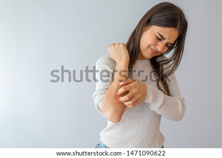 Women scratch the itch with hand , Concept with Healthcare And Medicine. Woman scratching arm on grey background. Allergy symptoms. Woman scratching her arm. #1471090622