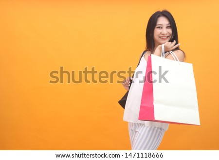 Isolated shot of pretty adult woman with shopping bag, wears casual outfit, dressed casually, Beautiful Asian models over yellow  background for advertising concept #1471118666
