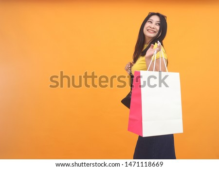 Isolated shot of pretty adult woman with shopping bag, wears casual outfit, dressed casually, Beautiful Asian models over yellow  background for advertising concept #1471118669