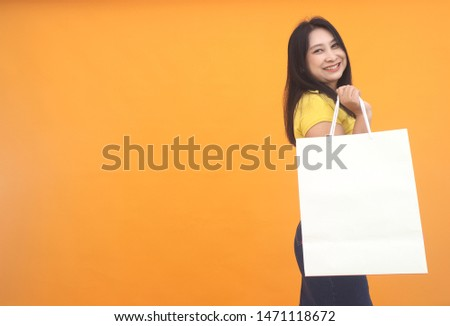 Isolated shot of pretty adult woman with shopping bag, wears casual outfit, dressed casually, Beautiful Asian models over yellow  background for advertising concept #1471118672