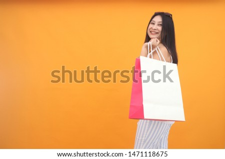 Isolated shot of pretty adult woman with shopping bag, wears casual outfit, dressed casually, Beautiful Asian models over yellow  background for advertising concept #1471118675