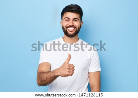Happy bearded man in stylish white T-shirt with beaming smile showing thumb up, isolated over blue background, studio shot. good job, well done. agreement concept #1471126115