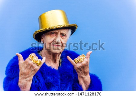 Funny and extravagant senior woman posing on colored background - Youthful old woman in the sixties having fun and partying #1471128170