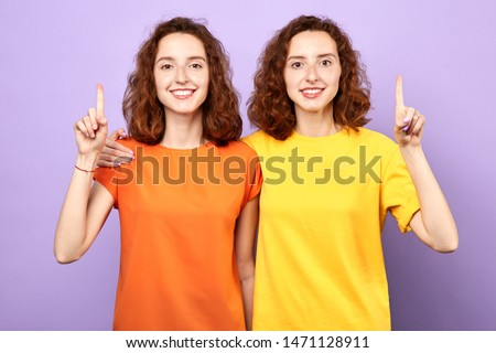 Happy beautiful twins girls point up isolated on blue background, two sisters showing something above their heads , advertisement, place for text, body language