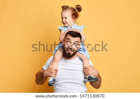 positive handsome daddy carries his kid on shoulders, enjoying time together. weekend, day off, entertainment concept. isolated yellow background #1471130870
