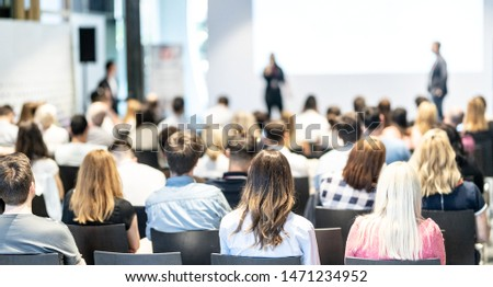 Business and entrepreneurship symposium. Speaker giving a talk at business meeting. Audience in conference hall. Rear view of unrecognized participant in audience. #1471234952
