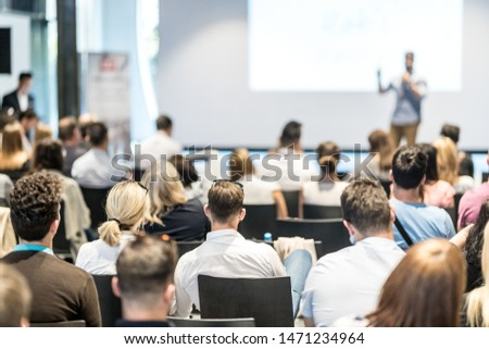 Business and entrepreneurship symposium. Speaker giving a talk at business meeting. Audience in conference hall. Rear view of unrecognized participant in audience. #1471234964