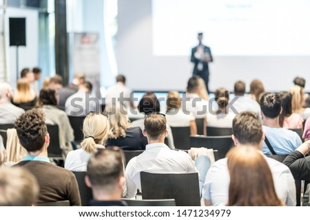 Business and entrepreneurship symposium. Speaker giving a talk at business meeting. Audience in conference hall. Rear view of unrecognized participant in audience. #1471234979