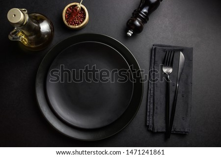Elegant black table setting: plates, napkin and silverware over black background. Flat lay. copy space #1471241861