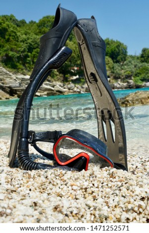 Snorkeling device with flippers and tubes with a beautiful background of the sea in the background                                 #1471252571