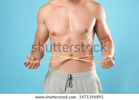 Young man with slim body using measuring tape on light blue background, closeup view #1471346891