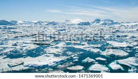 Iceberg and ice from glacier in arctic nature landscape on Greenland. Aerial photo drone photo of icebergs in Ilulissat icefjord. Affected by climate change and global warming. Royalty-Free Stock Photo #1471369001