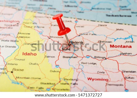 Red clerical needle on a map of USA, Montana and the capital of Helena. Close up Montana map with red tack US map pin #1471372727